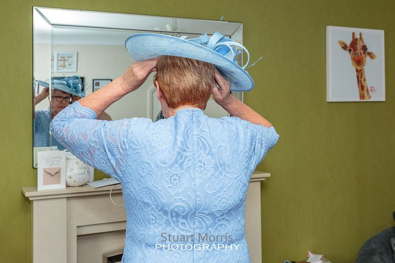 the brides mother stands looking in the mirror as she adjusts her wedding hat