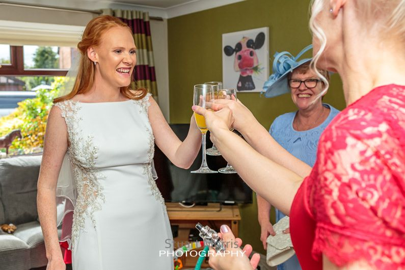 the bride clinks glasses with the bridesmaids before setting off from home to the ceremony