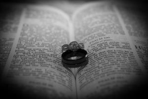 Close up black and white picture of a husband's and wive's wedding ring sitting on the fold of an open bible
