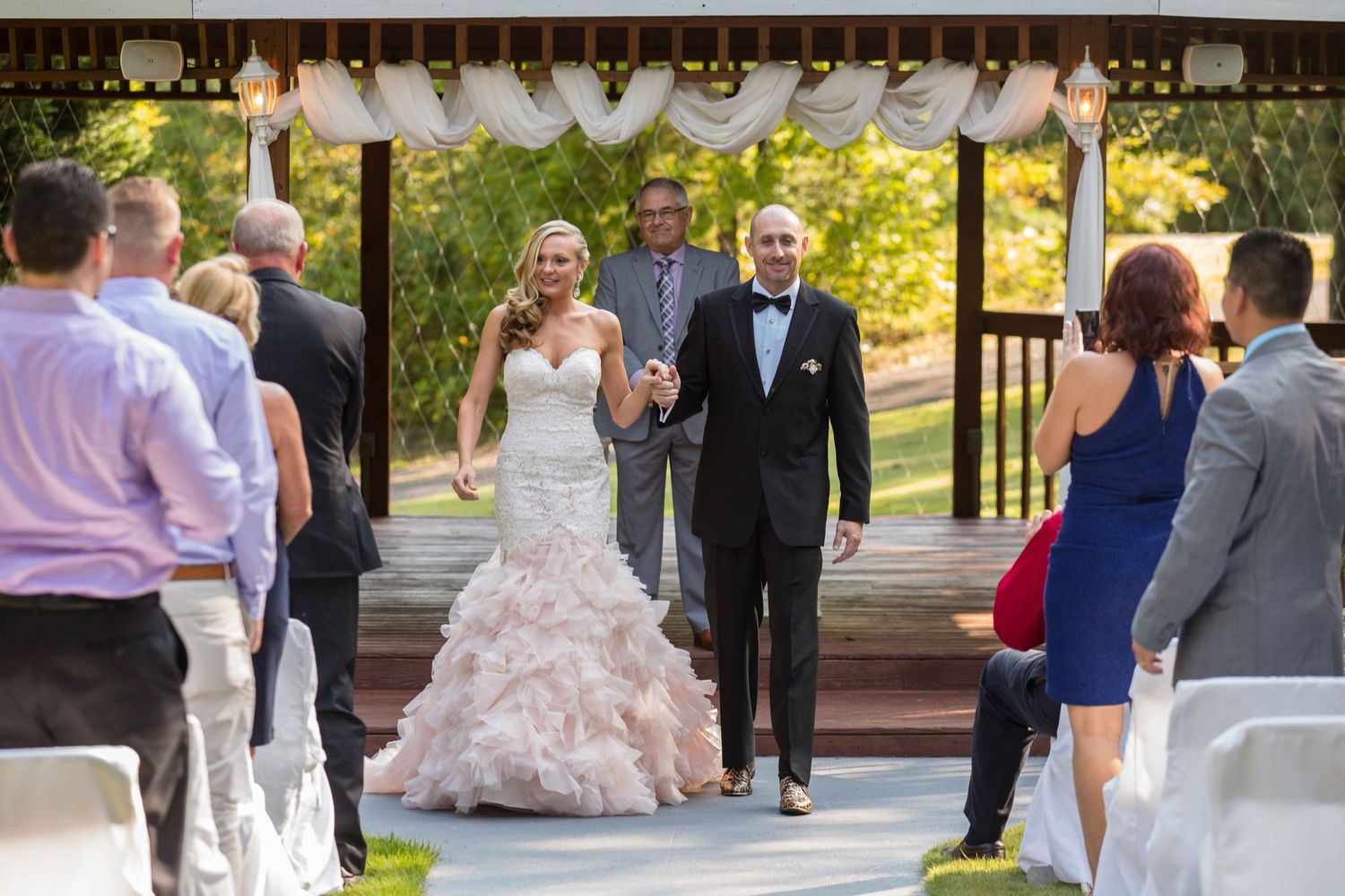 Newlyweds leaving their wedding with guests standing and applauding the just married couple.  Pink Wedding Dress