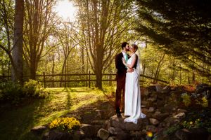 Groom in black tux, bride in white wedding gown embrace in the woods with sun shining brightly behind them
