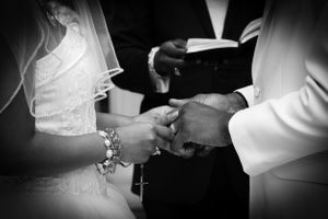 close up black and white picture of a couple holding hands in front of officiants bible during a wedding