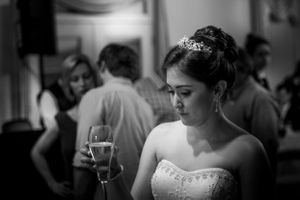 Young bride in strapless wedding dress and tiara looking at her glass of champagne in a black and white picture