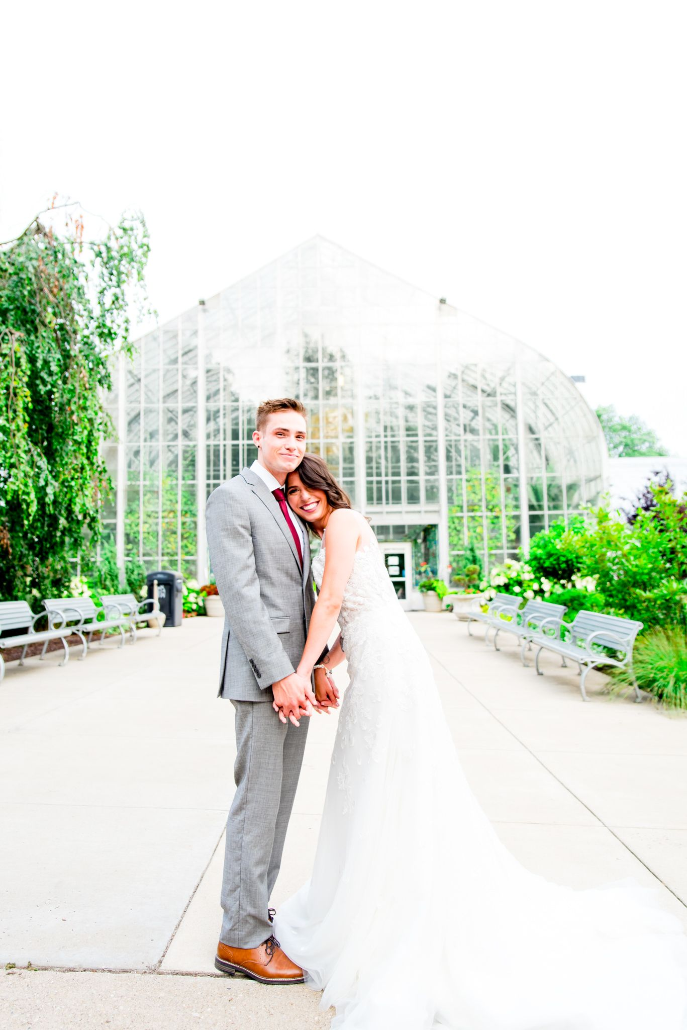 bride lays on groom's chest and they smile in front of Krohn Conservatory for summer wedding in Cincinnati