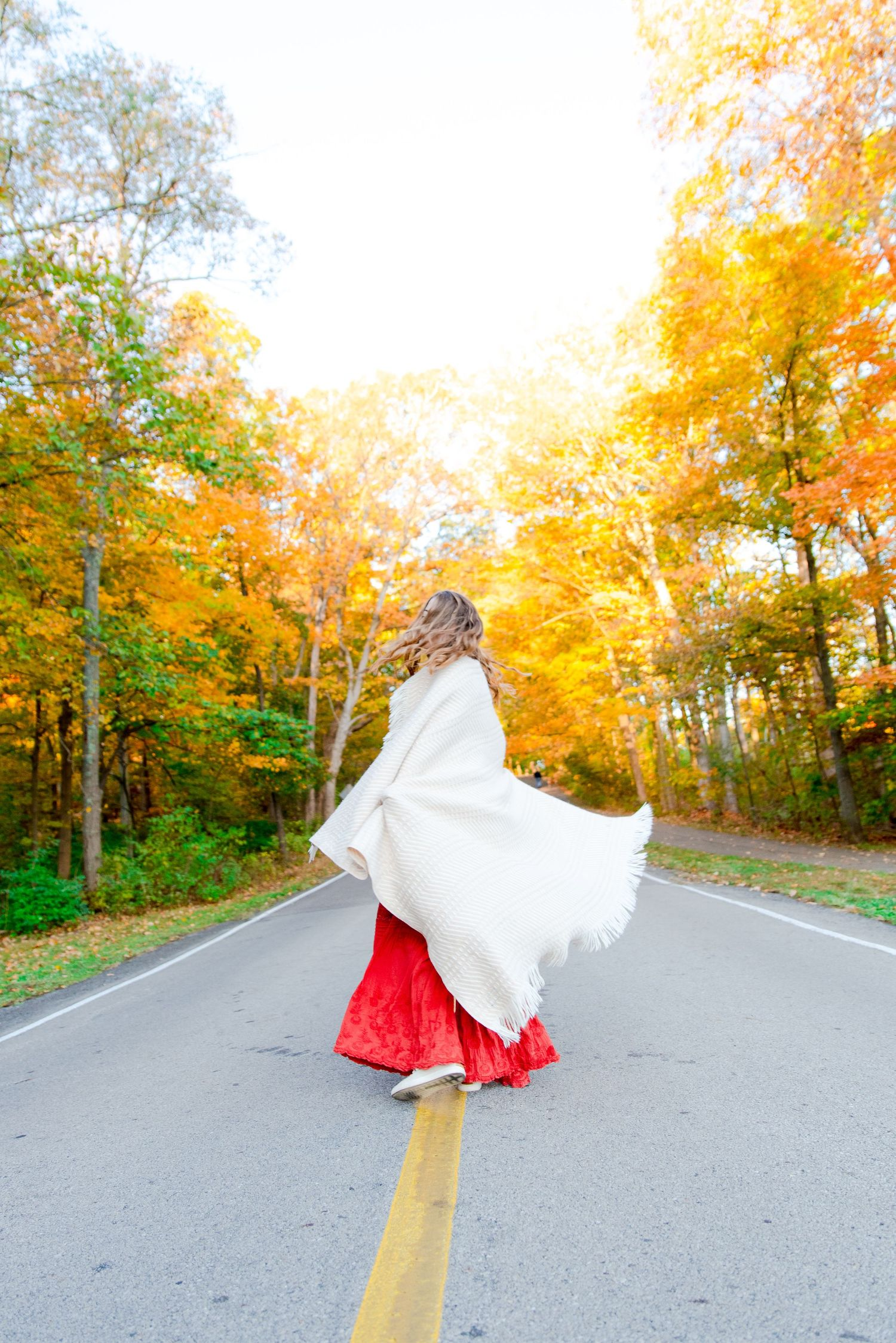 girl wrapped in cream blanket dancing in the road surrounded by yellow trees at Sharon Woods