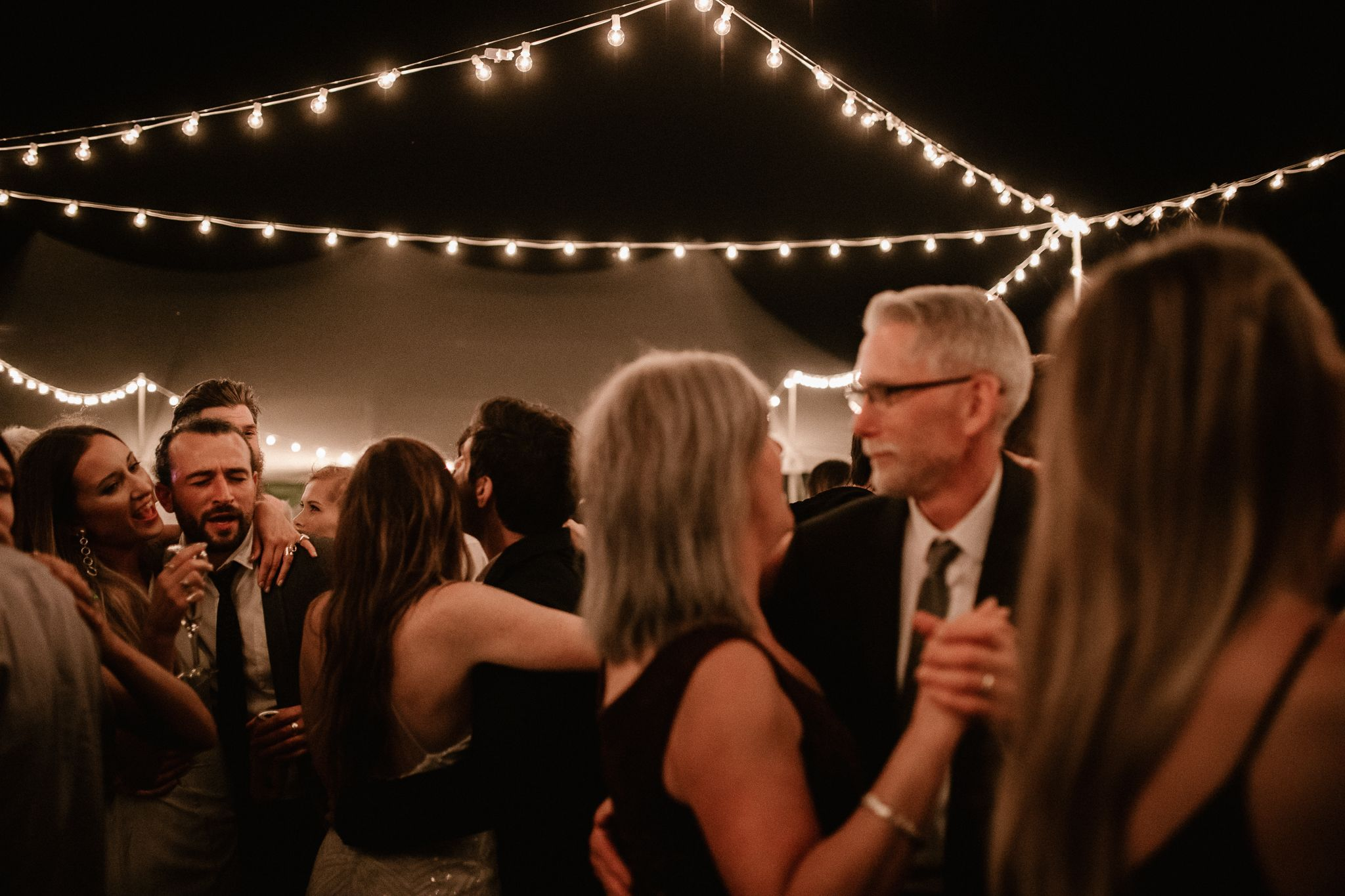 Toronto wedding guests singing and danging the night away in the moonlight under dimly lit string lights.
