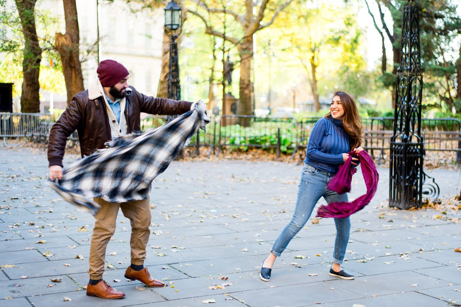 young engaged couple smiles and throws their scarves at each other for engagement pictures in NYC Manhattan