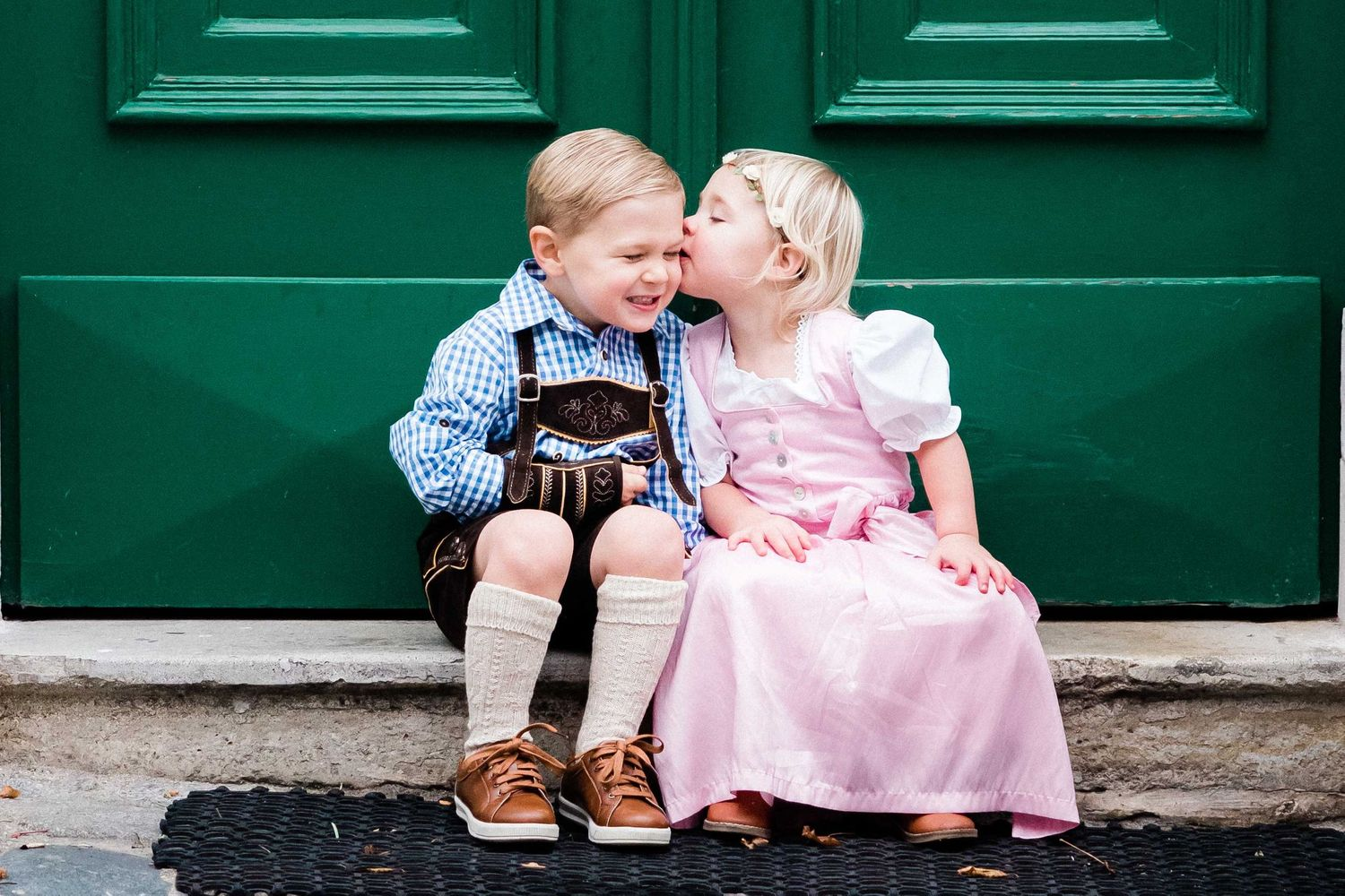Children sitting in Vienna in front of a green door wearing traditional outfit Lederhosen and Dirndl