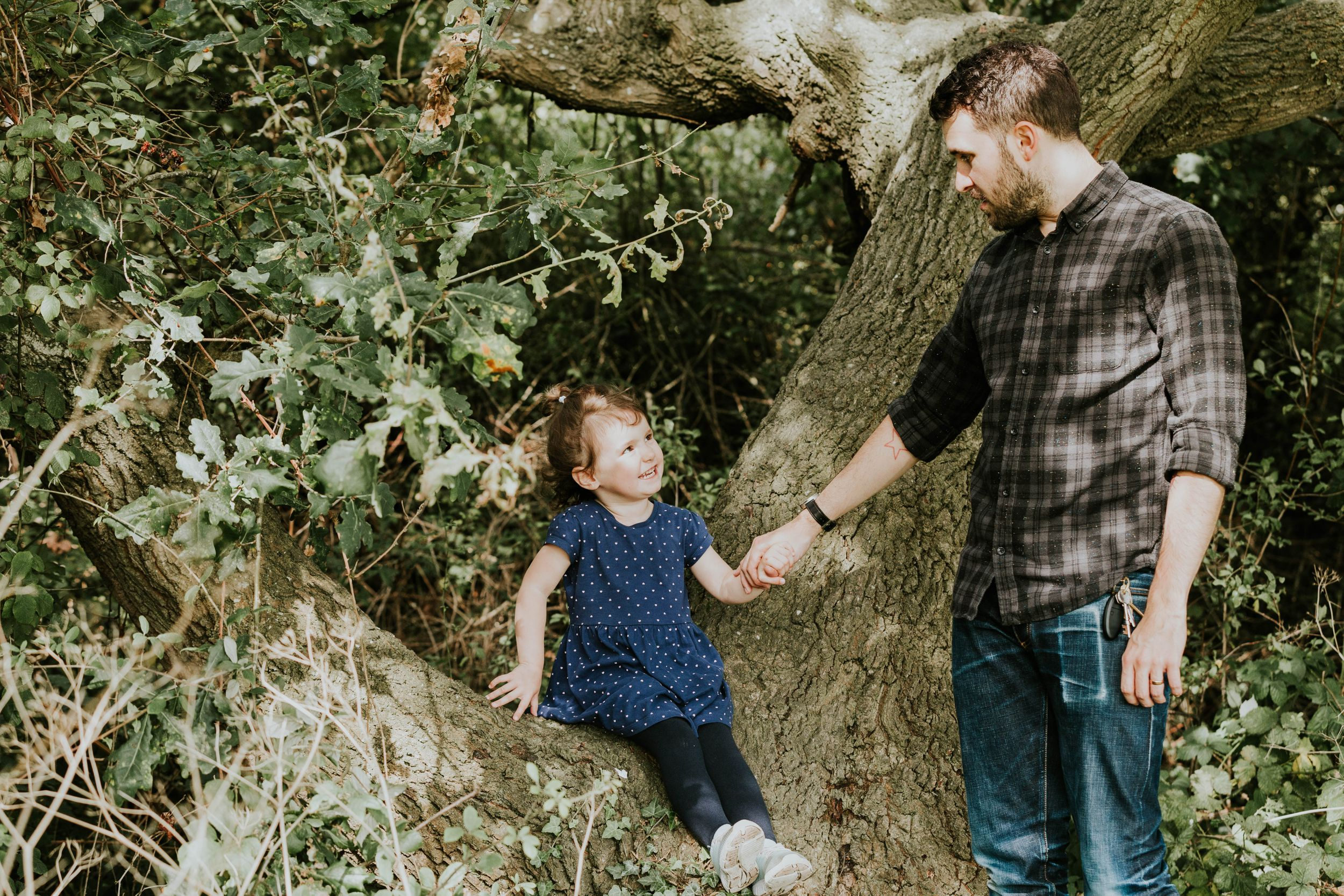 dad and daughter in forest holding hands