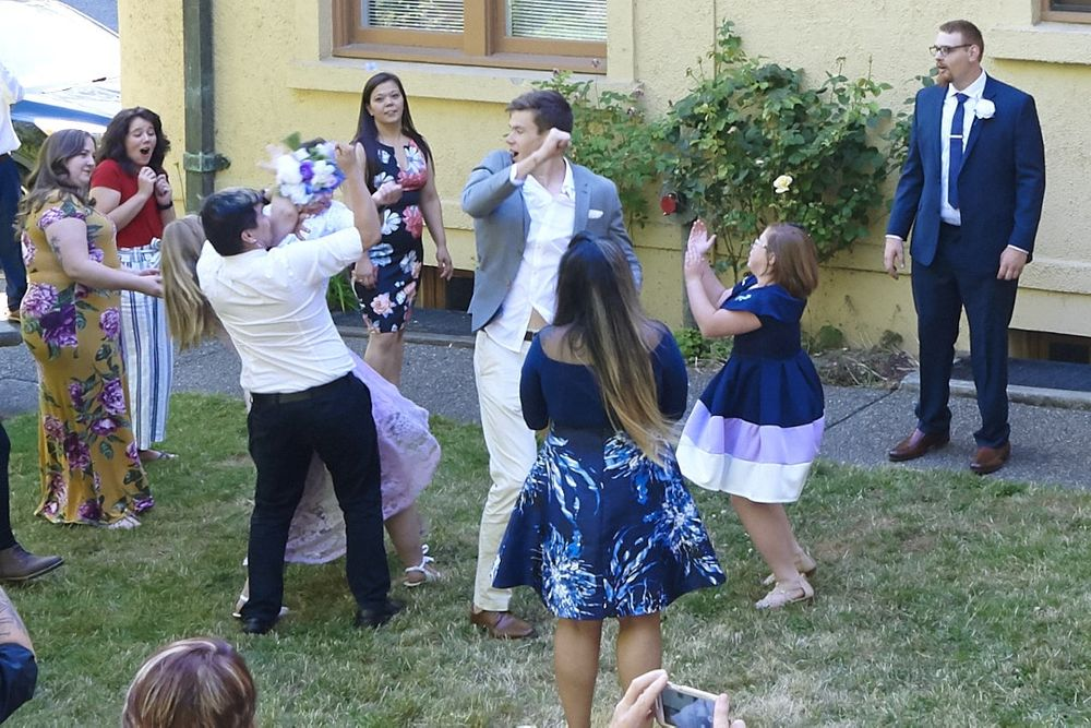 Groomsmen catches bouquet but runs into bridesmaid during bouquet toss at Lord Mansion, Olympia, WA