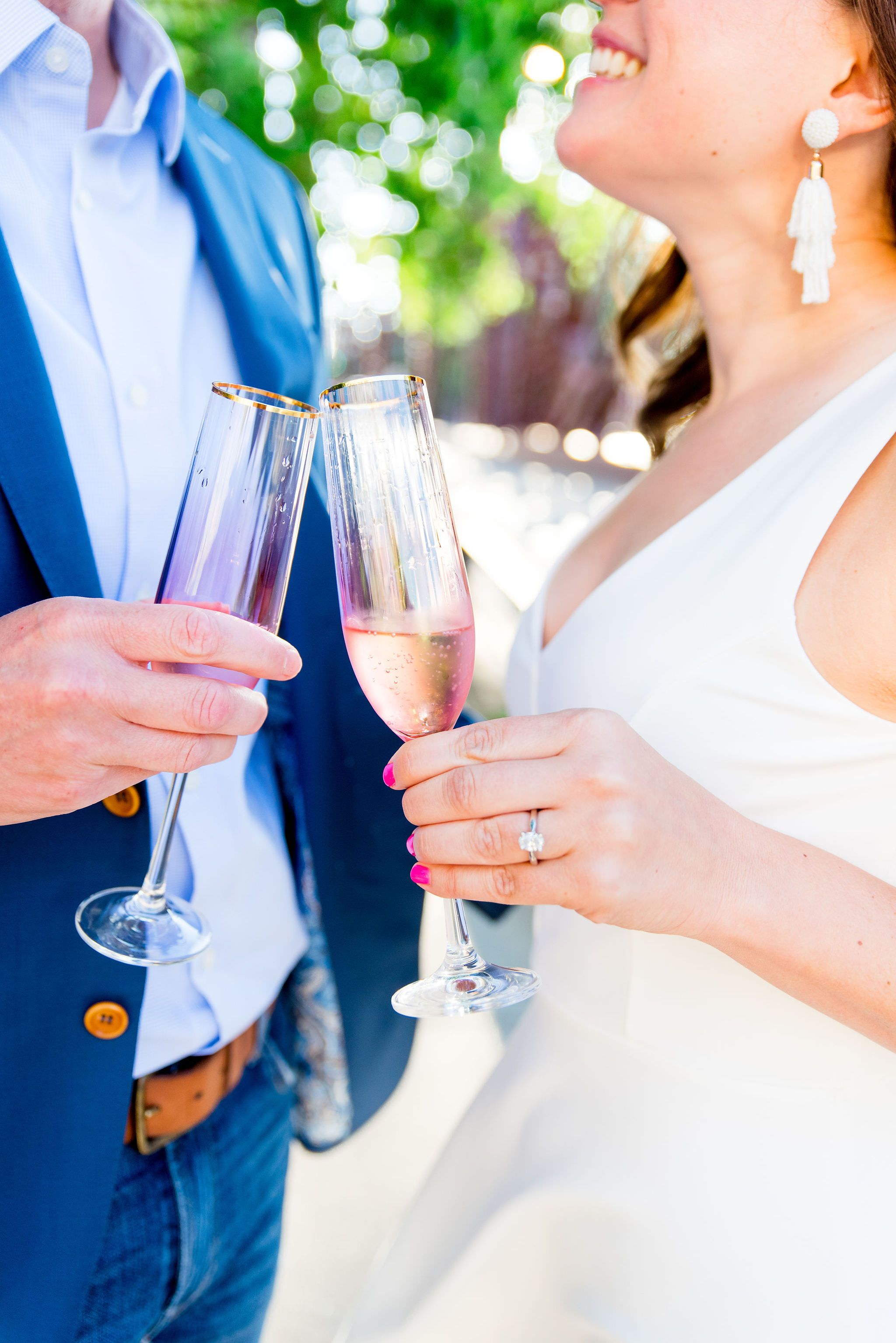engaged couple clinking pink and gold champagne glasses from anthropologie at Kinzie St Bridge engagement pictures