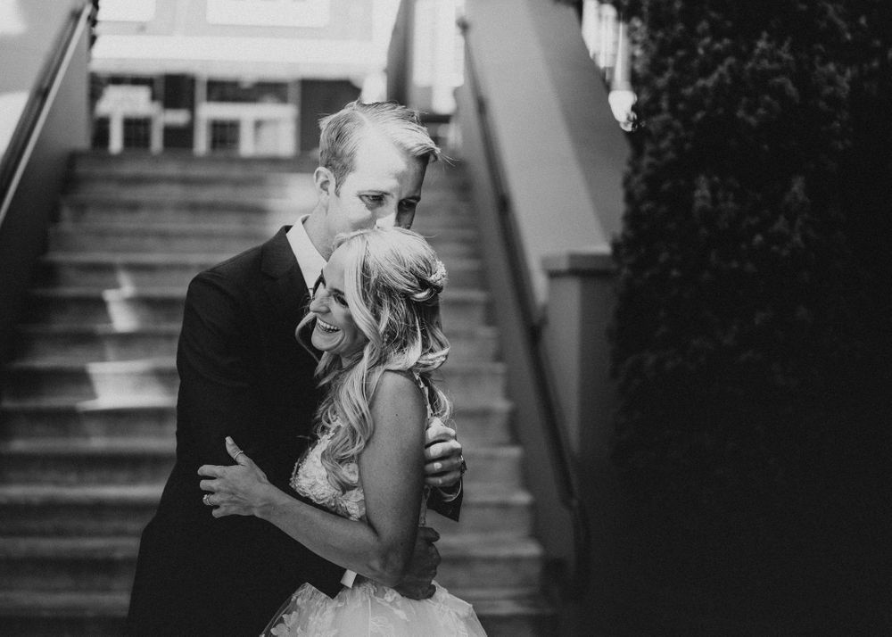 Bride and Groom share a hug and a laugh at the base of the steps of Fifth Street Market in Eugene, OR
