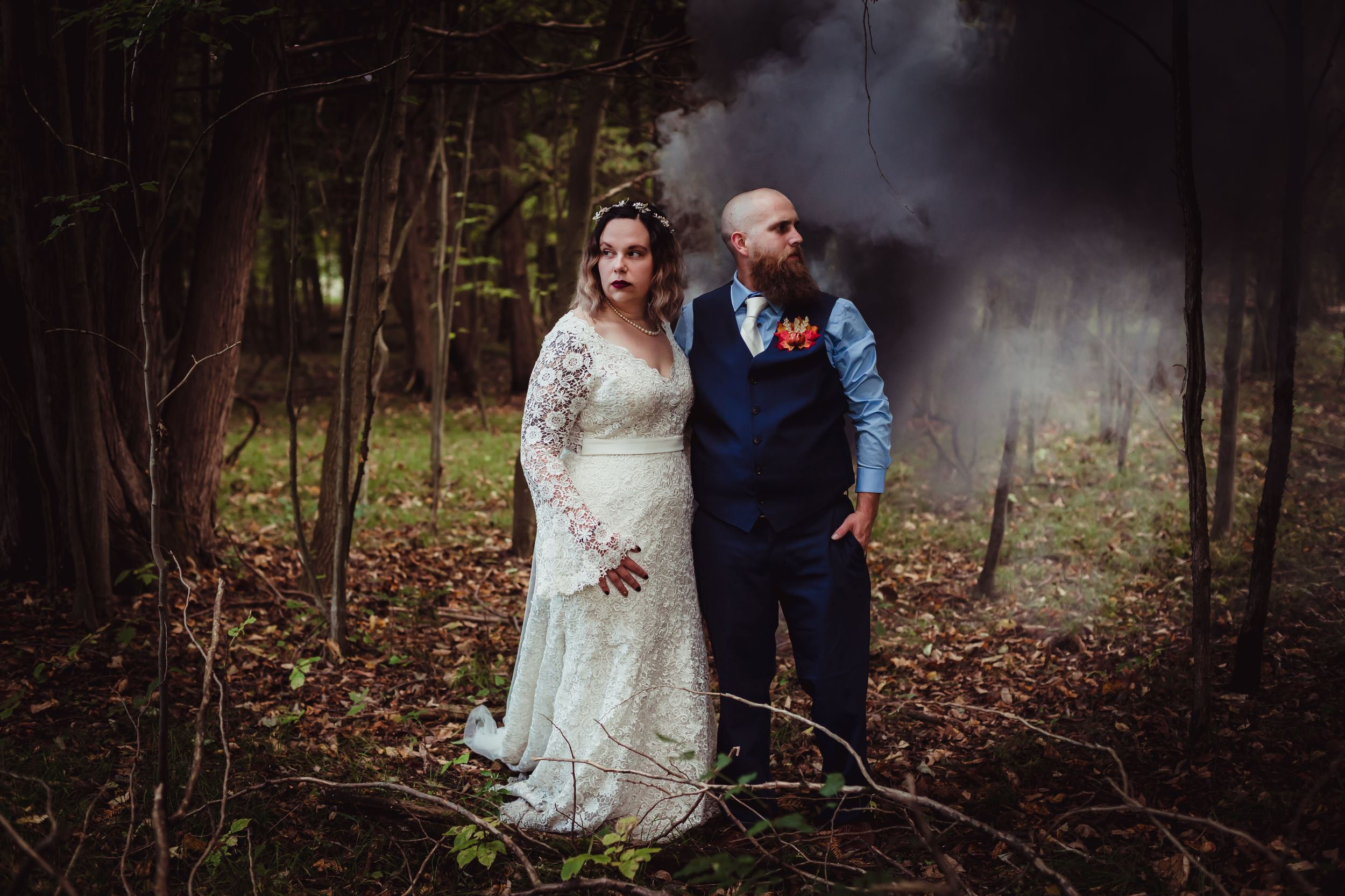 Woman and man in wedding attire standing in the woods with black smoke behind them.