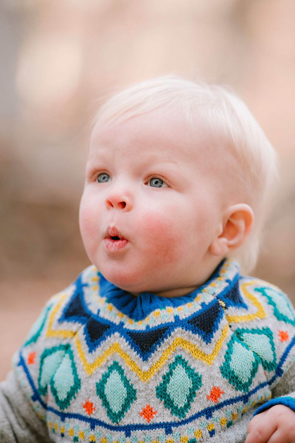Cute toddler in a sweater makes a funny face