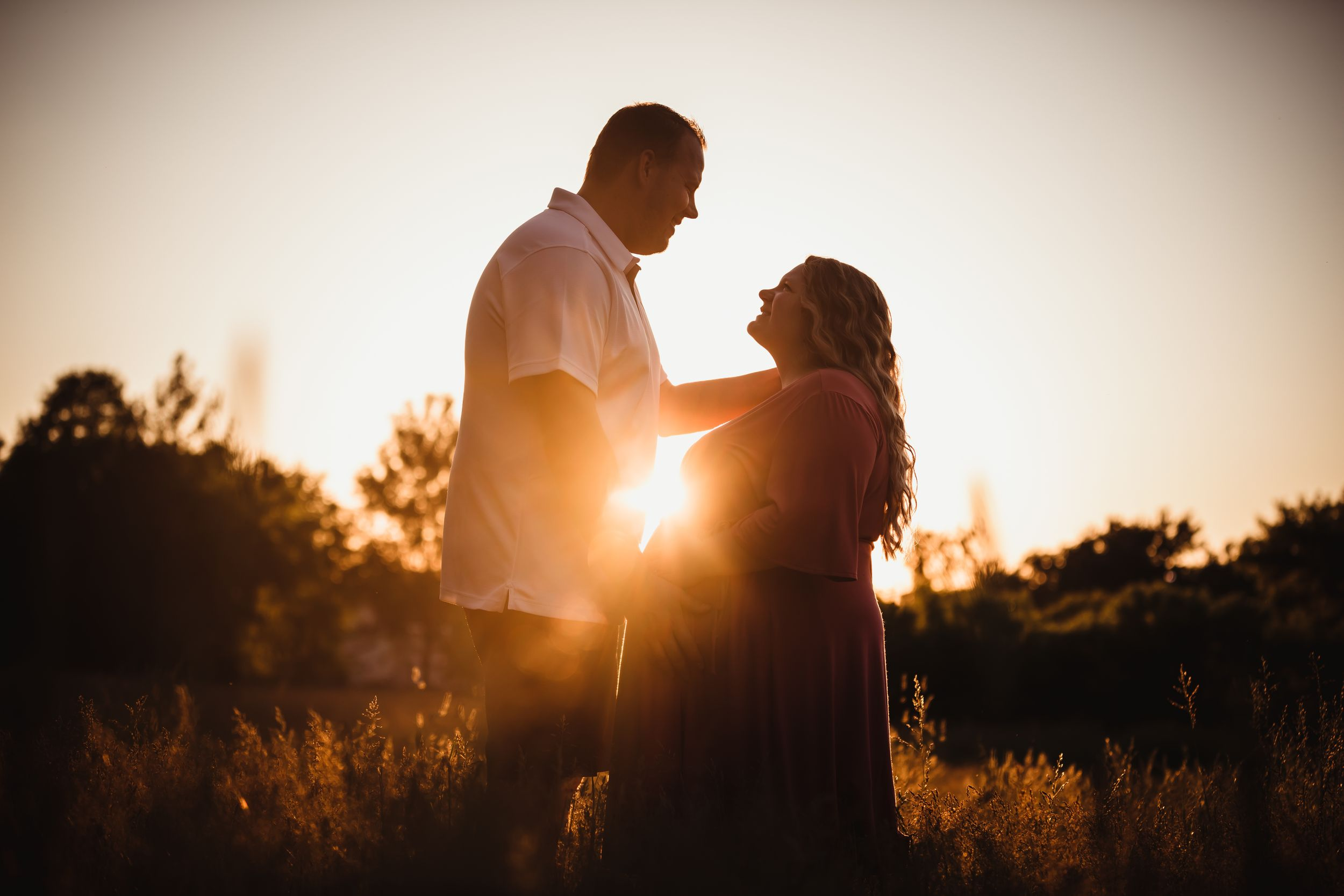 Man and pregnant woman looking at each other smiling in a field at sunset.