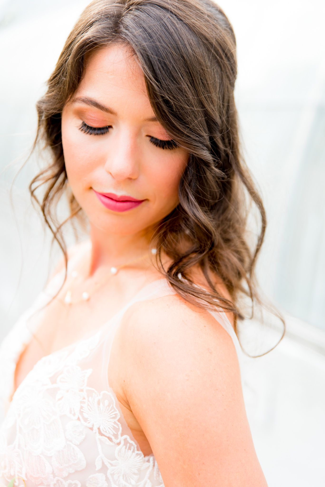 bride in pink lipstick, lace wedding gown, and pearl necklace in front of all white Krohn Conservatory wedding