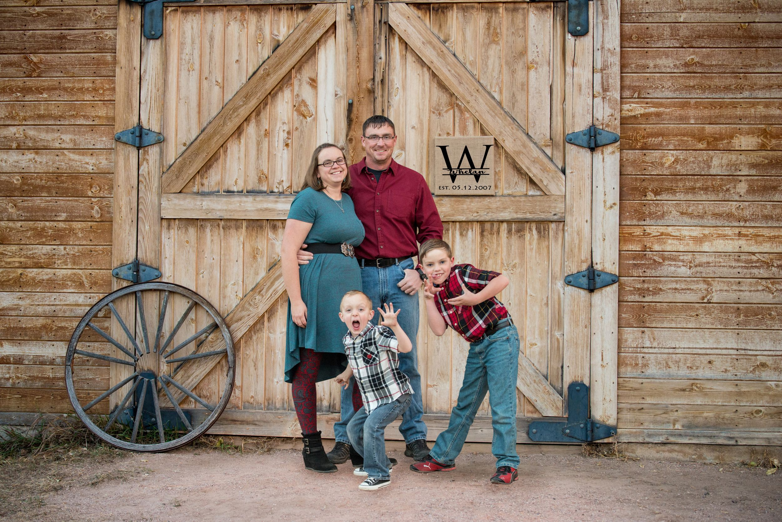 Family of 4 getting family photos in front of the beautiful barn at Rock Ledge Ranch in Colorado Springs,CO