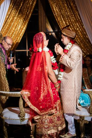 The groom places a necklace of black and gold beads on the bride