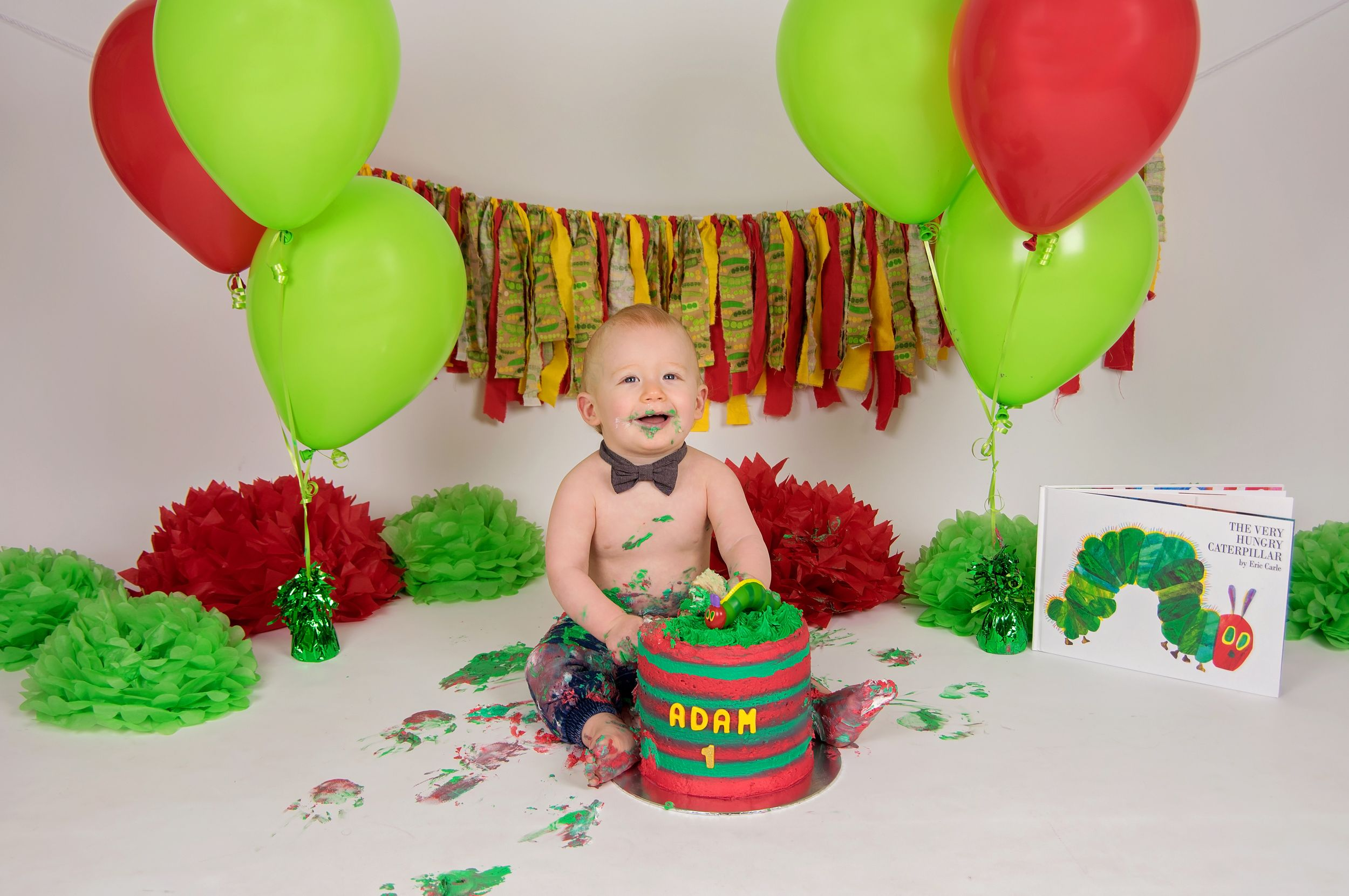 baby eating cake with red and green theme and decorations