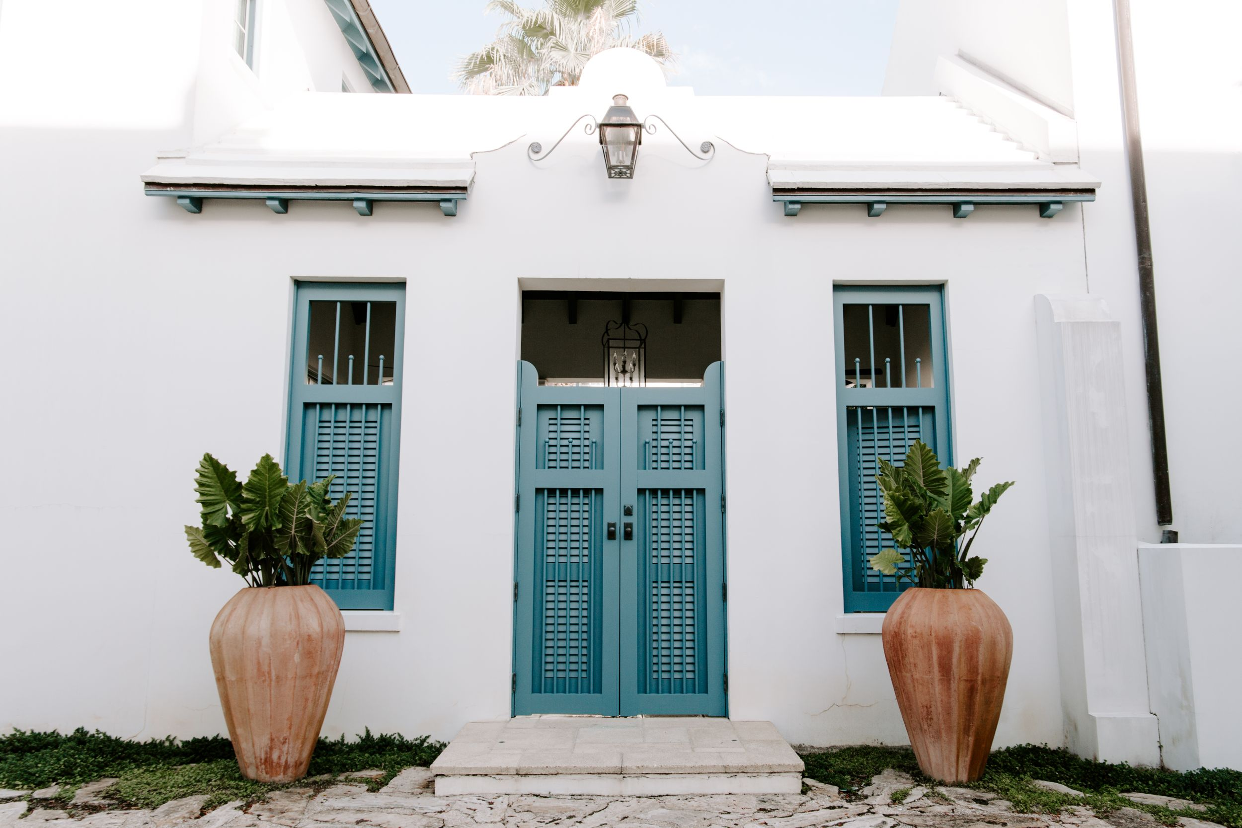 blue door on a white building with two plants, 30A weddings