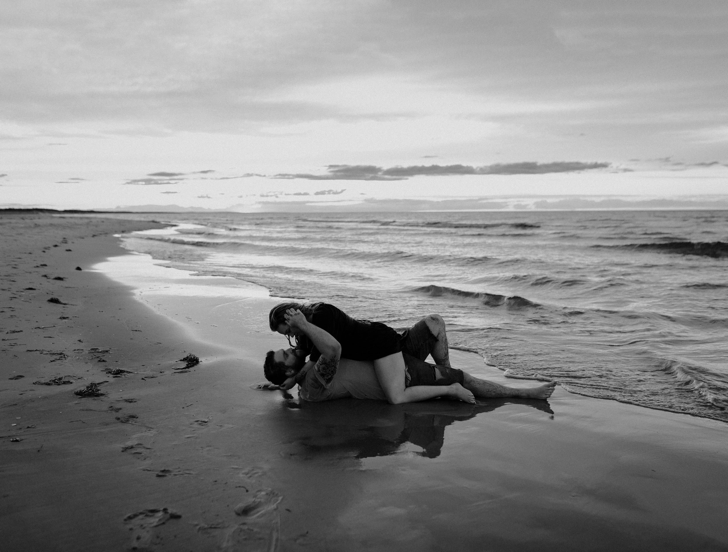 Black and white photo of steamy intimate couple on PEI beach rolling in the sand and looking into each other's eyes.