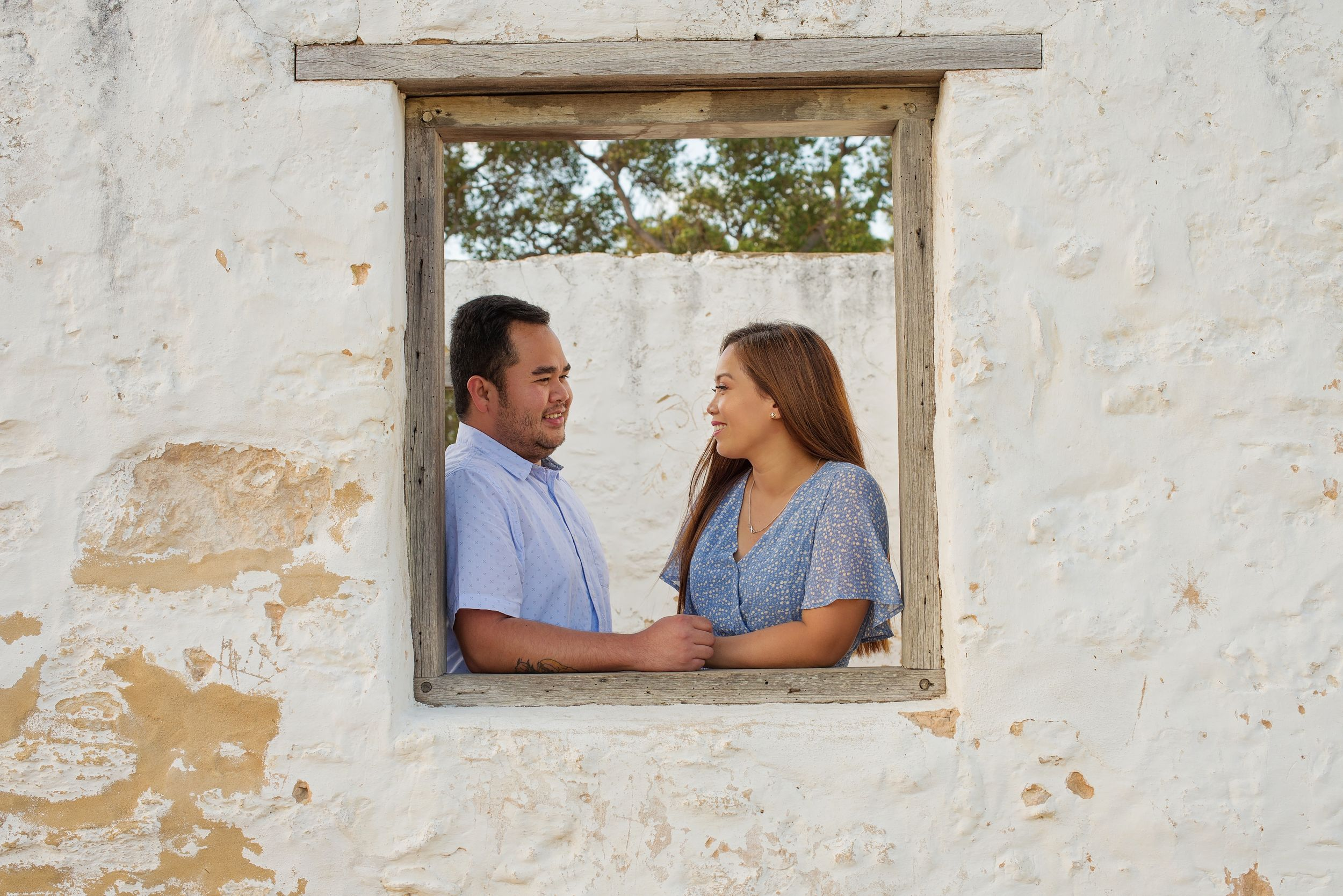 couple facing eachother standing in a window frame
