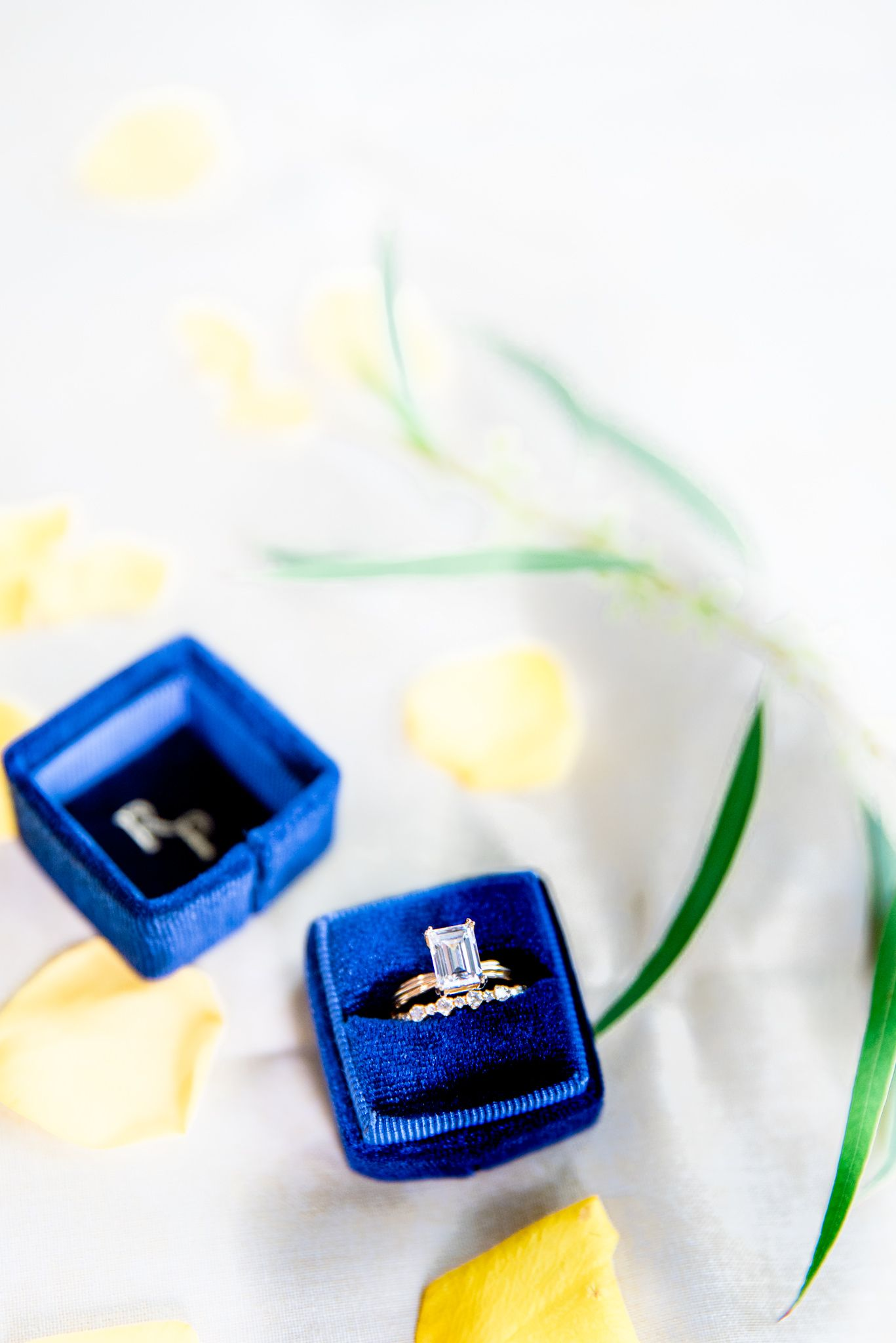 emerald cute diamond engagement ring and gold wedding ring in blue ring box next to greenery and yellow rose petals