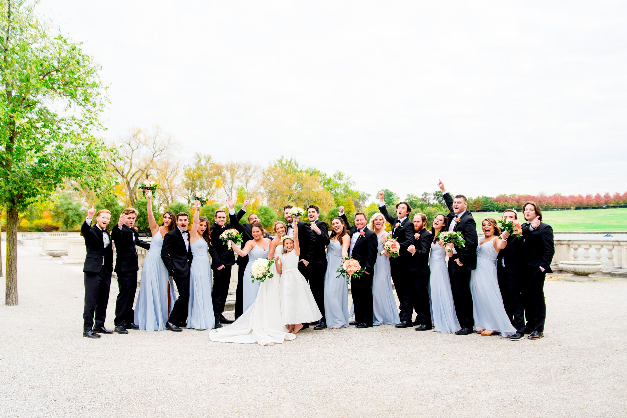 large wedding party in black suits and light blue dresses cheer on bride and groom at Forest Park in St. Louis
