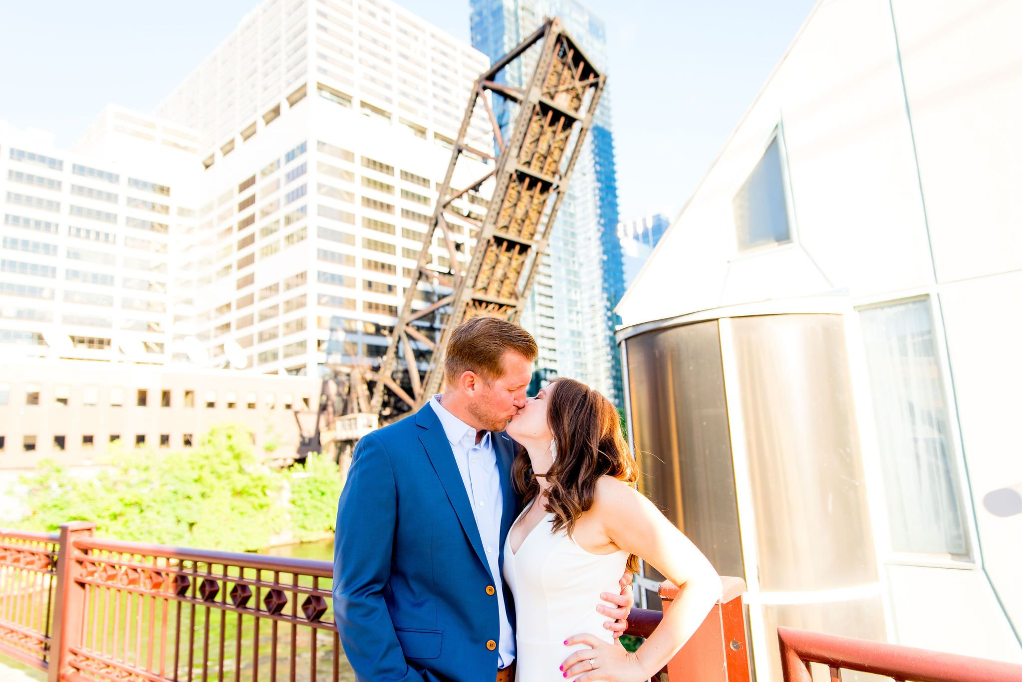 woman in white dress kissing man in navy suit in front of Chicago River at Kinzie St Bridge engagement pictures