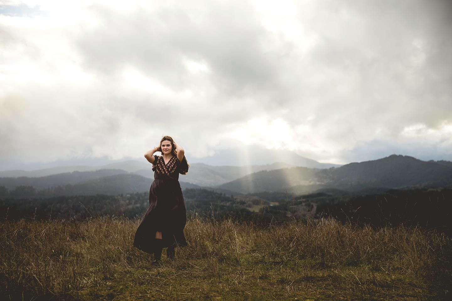 senior girl fixing her hair and walking on a golden grassy hill with mountains and clouds in the background