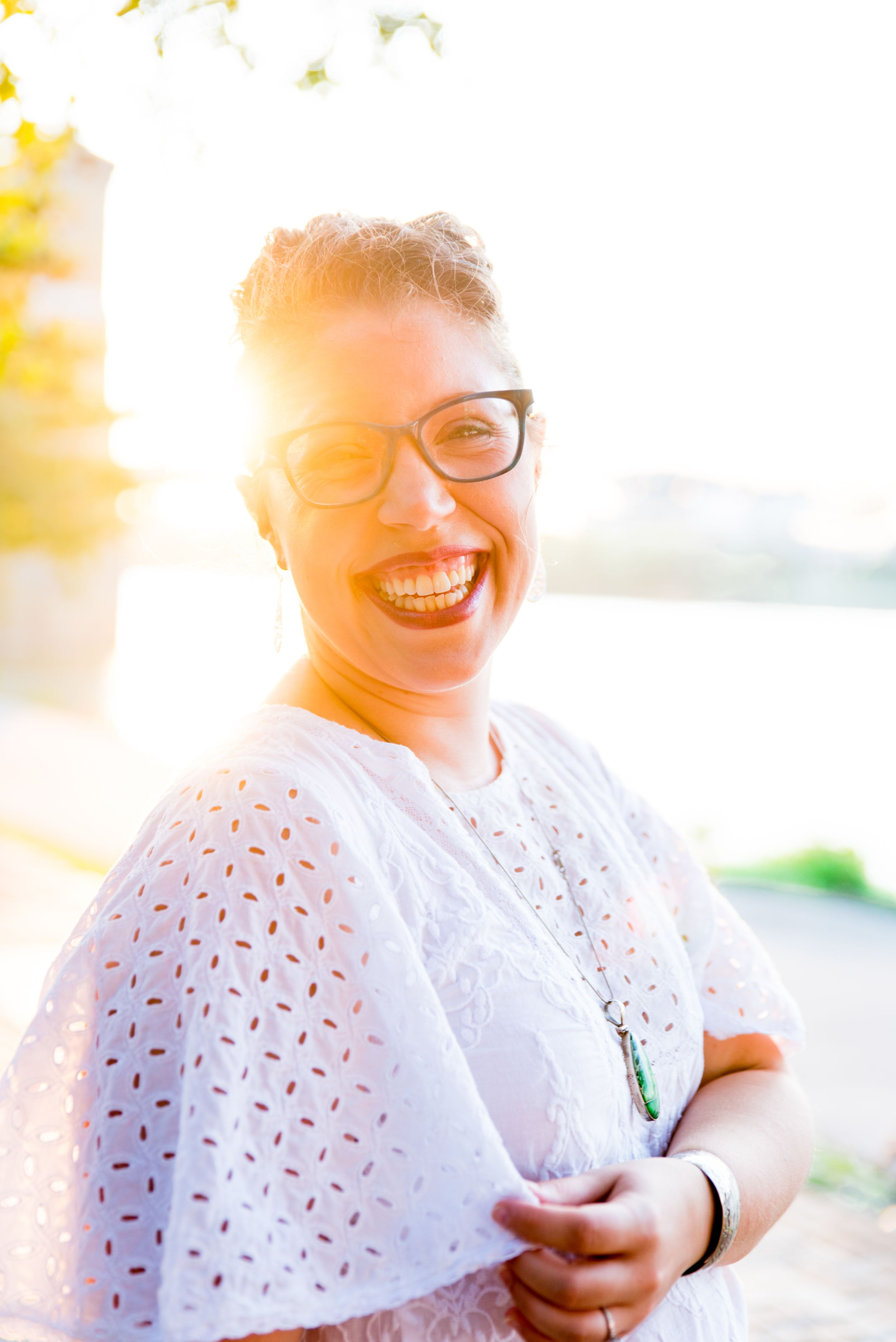 woman in white shirt, red lipstick, and glasses laughs and smiles in front of Roebling Bridge at sunset