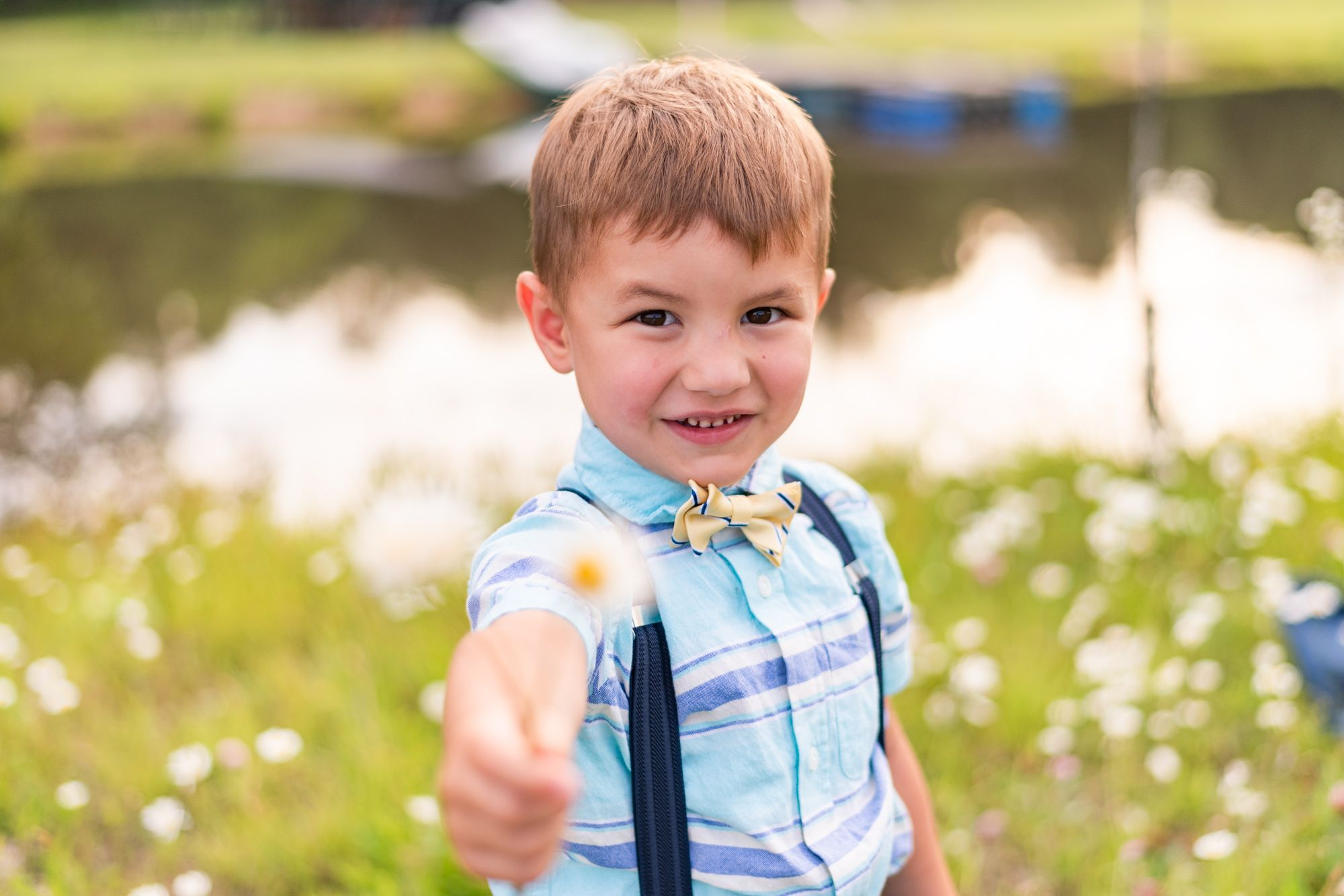 Little boy holding flower in front of pond in Clarion Pennsylvania