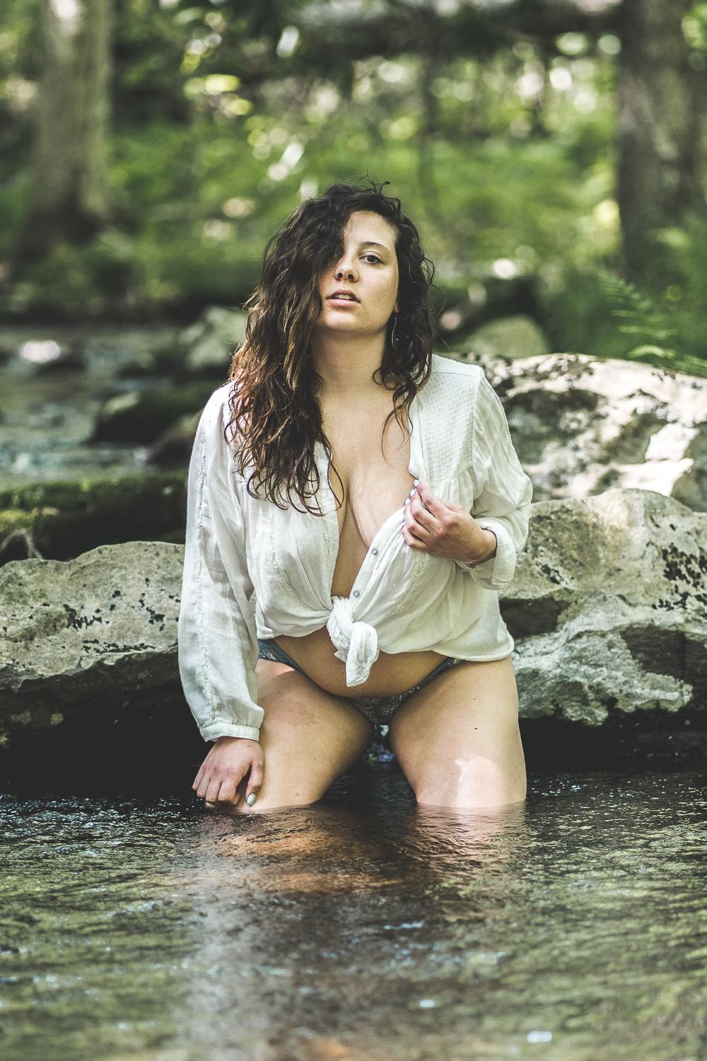 Outdoor boudoir session with girl on knees in creek pulling at white tie shirt in front of rocks in Poconos Mountain
