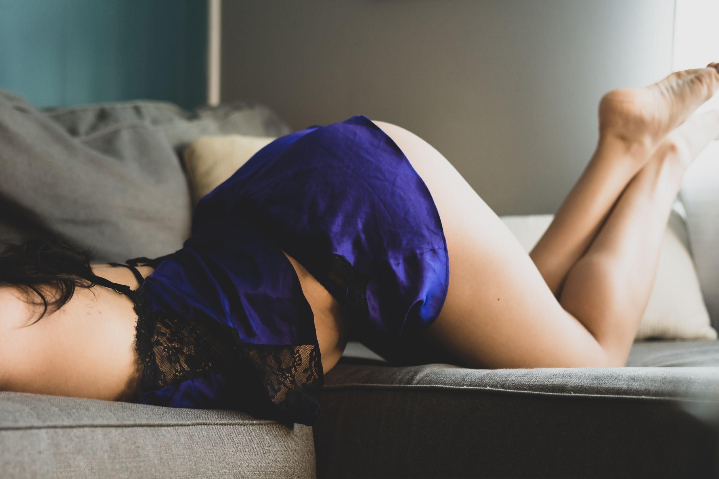 In-home boudoir session with female arching back and raising butt in purple lingerie for cozy boudoir session.
