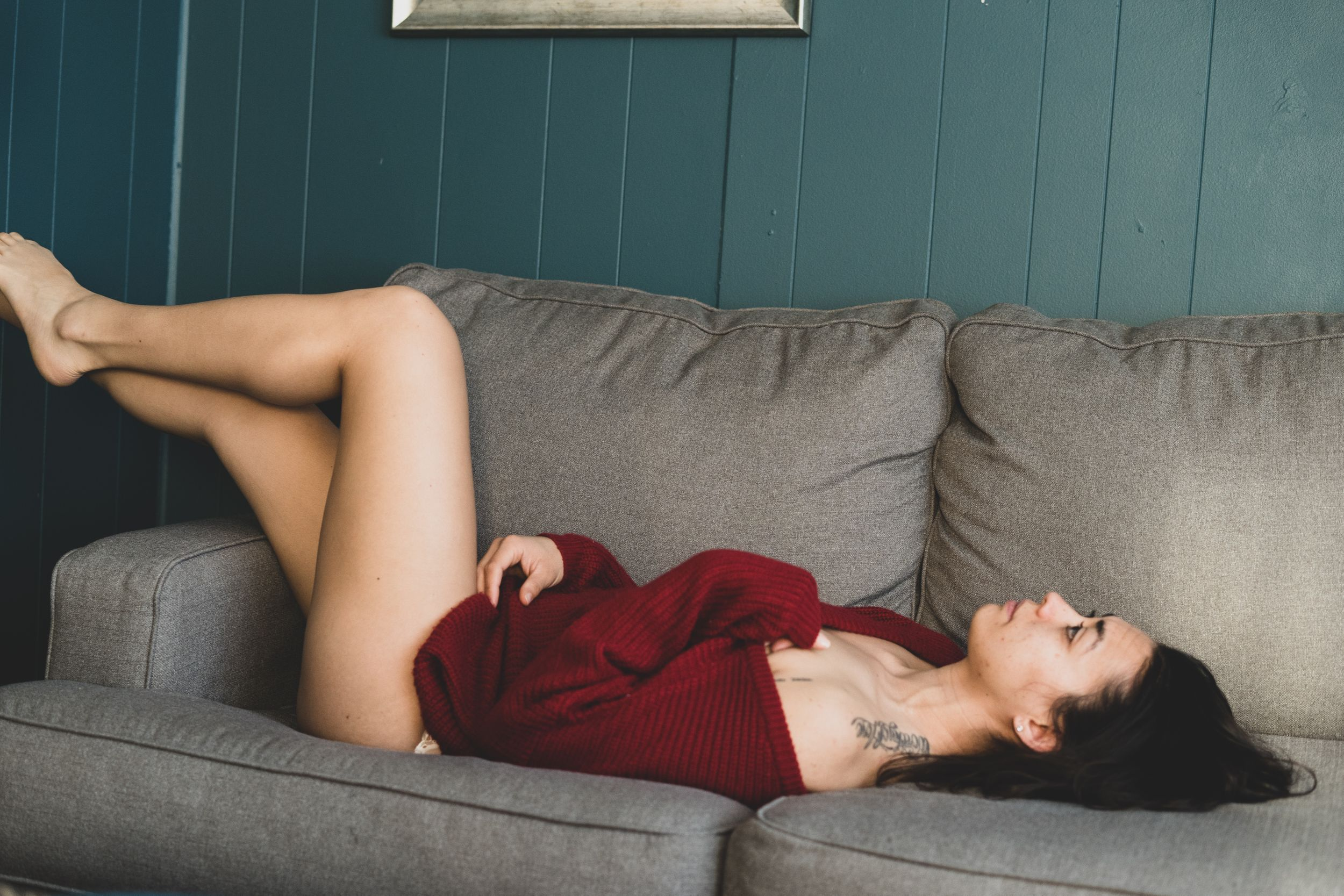 Fearless female session, boudoir session, in-home with cozy red sweater and laying on grey couch