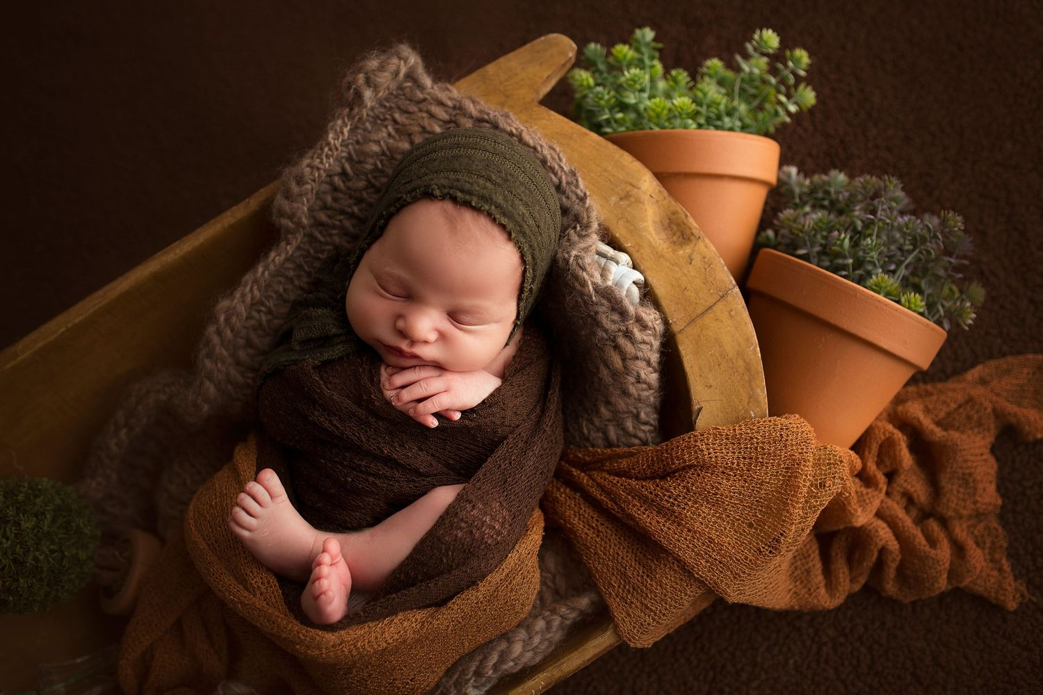 baby boy photoshoot wrapped in brown blanket in trench bowl