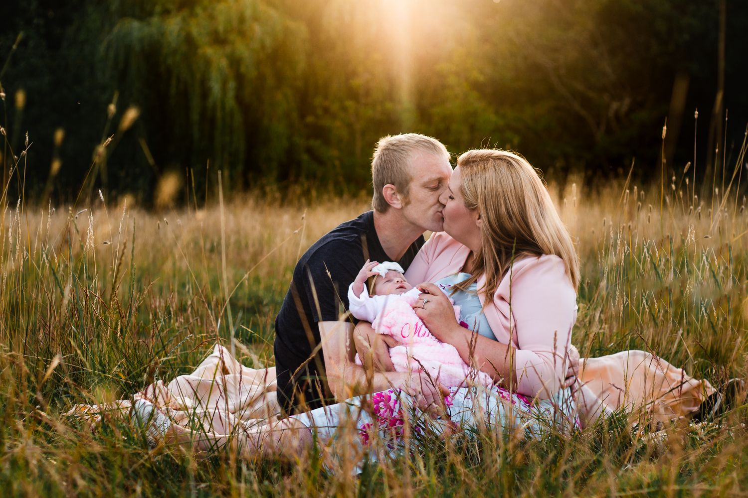 In a field in Havant at sunset new parents sit with their newborn daughter, kissing in the long grass.