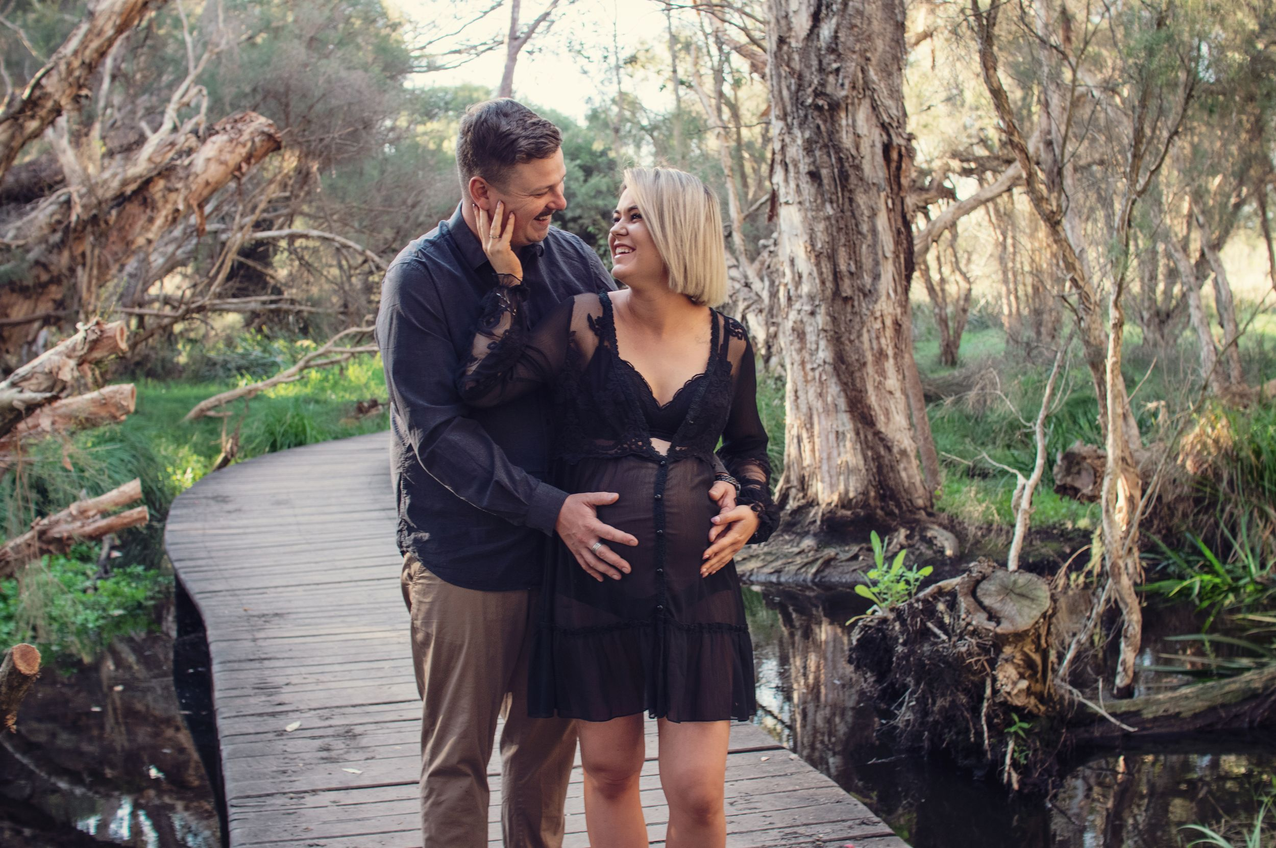 couple smiling and touching pregnant belly outside