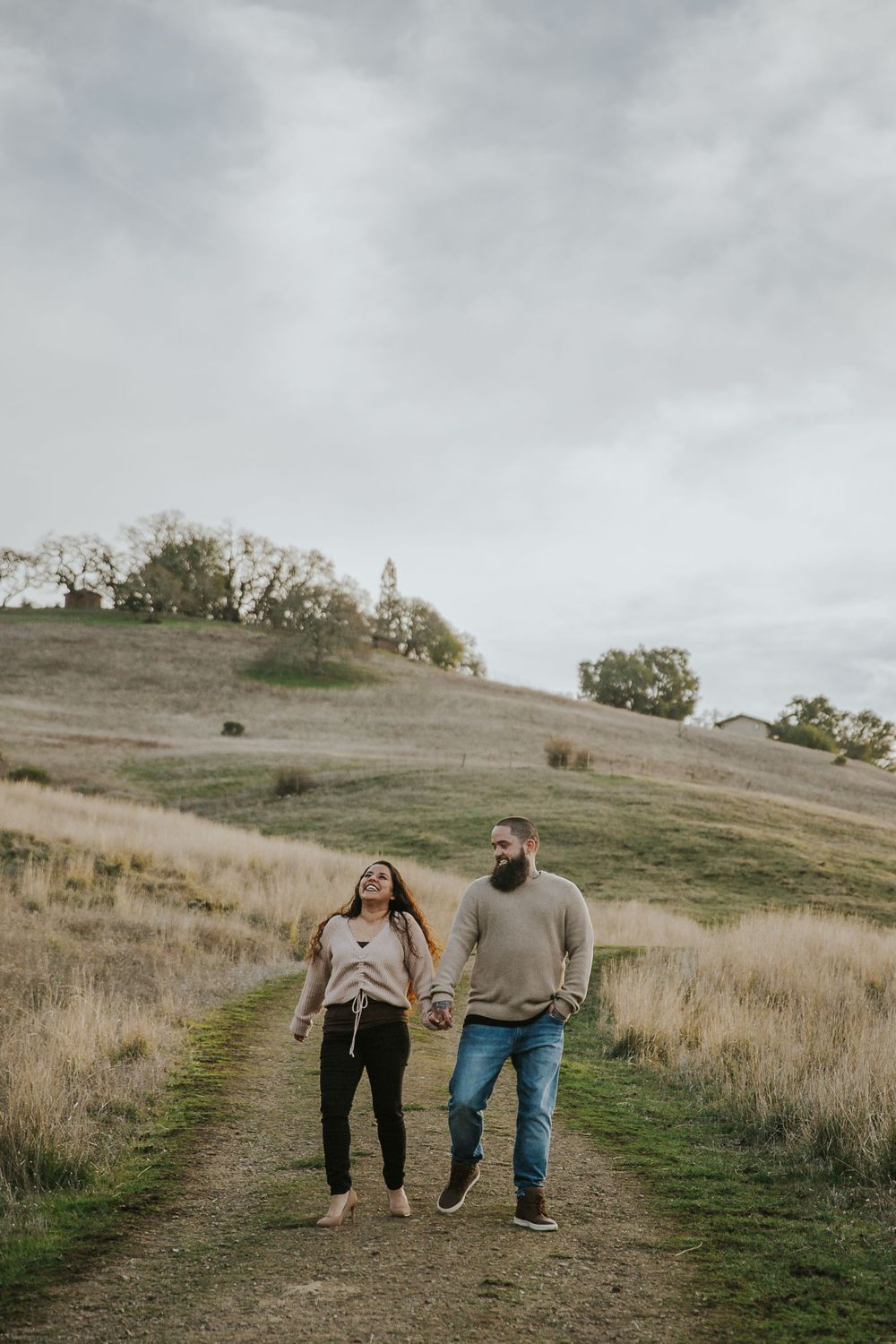 rebecca skidgel photographer engagement session at north sonoma mountain couple in field holding hands laughing walking