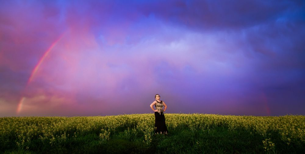 A graduate wearing a gown from Klassique Designs stands in a blooming canola field under a real rainbow