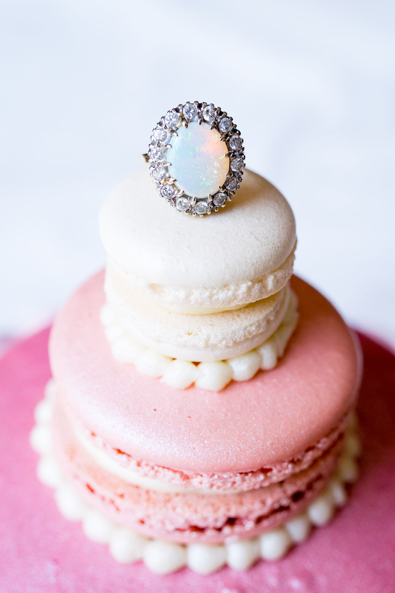 oval opal engagement ring on top of a tier giant macaron cake in pink and white