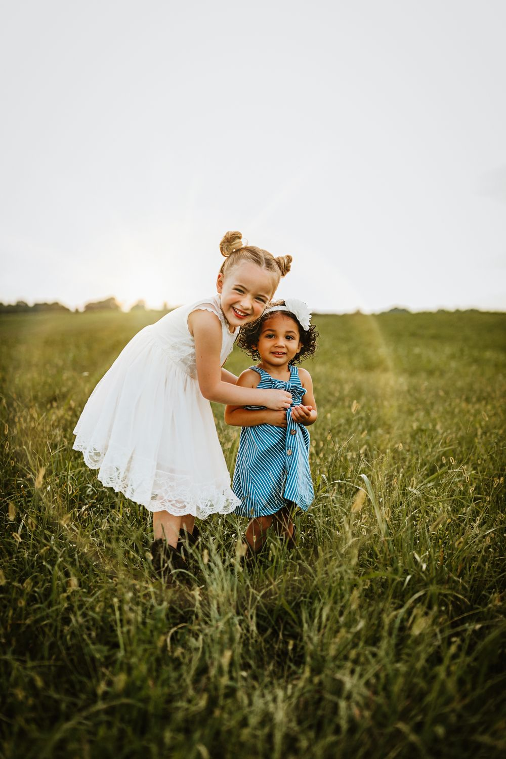 image by kylee swisher photography of sisters smiling in a field