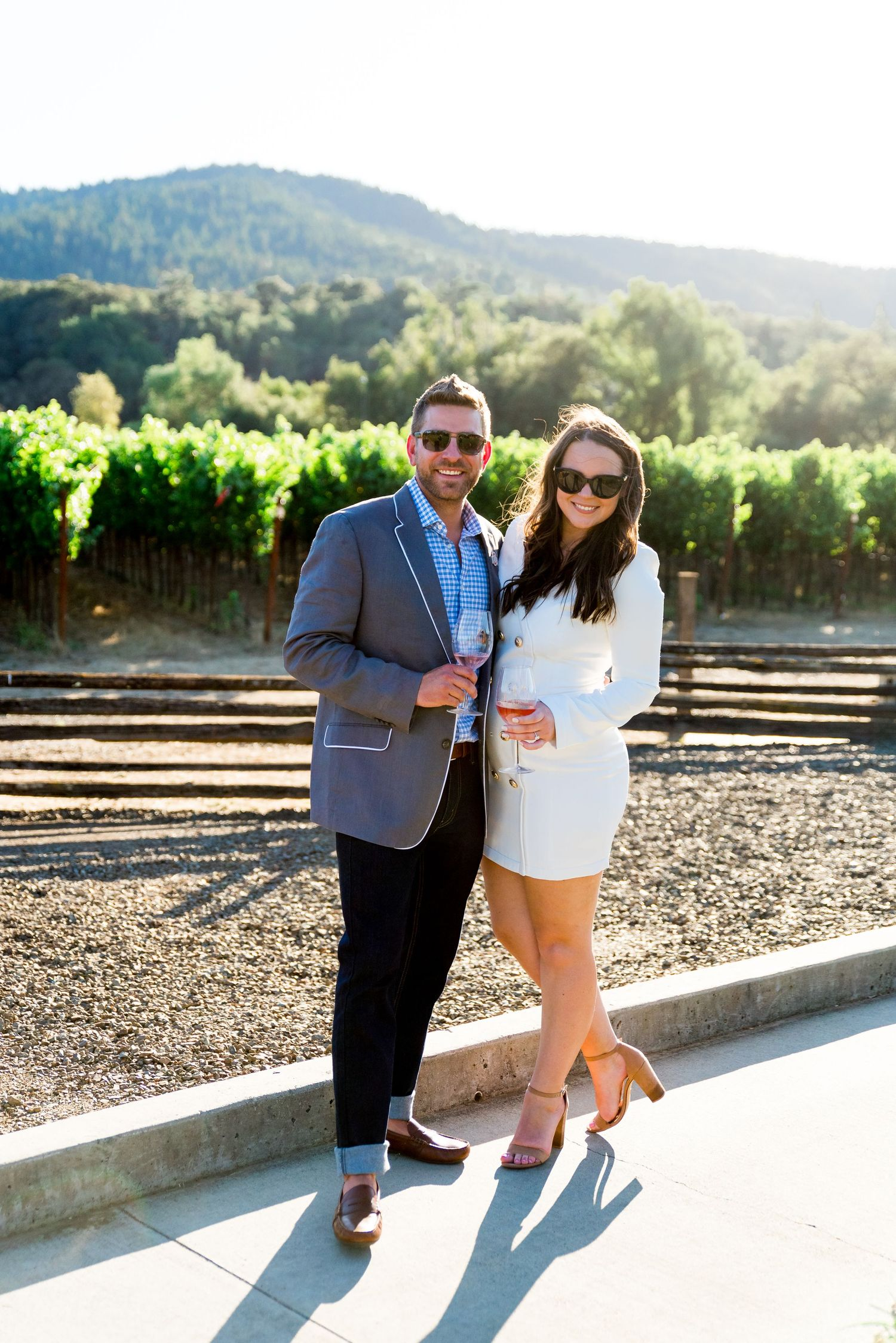 woman in white blazer minidress and man in grey suit holding wine glasses in front of vineyards at Pennyroyal Farm