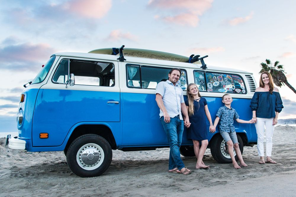 Image of a family standing in front of a classic VW Bus at the beach in Dana Point, CA