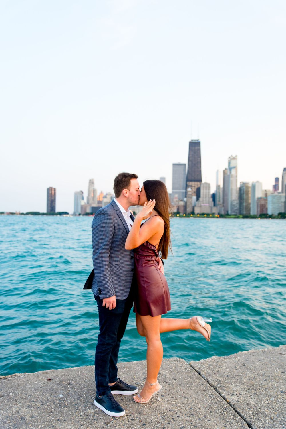 man and woman kissing and woman holding up hand in front of skyline after Chicago Proposal