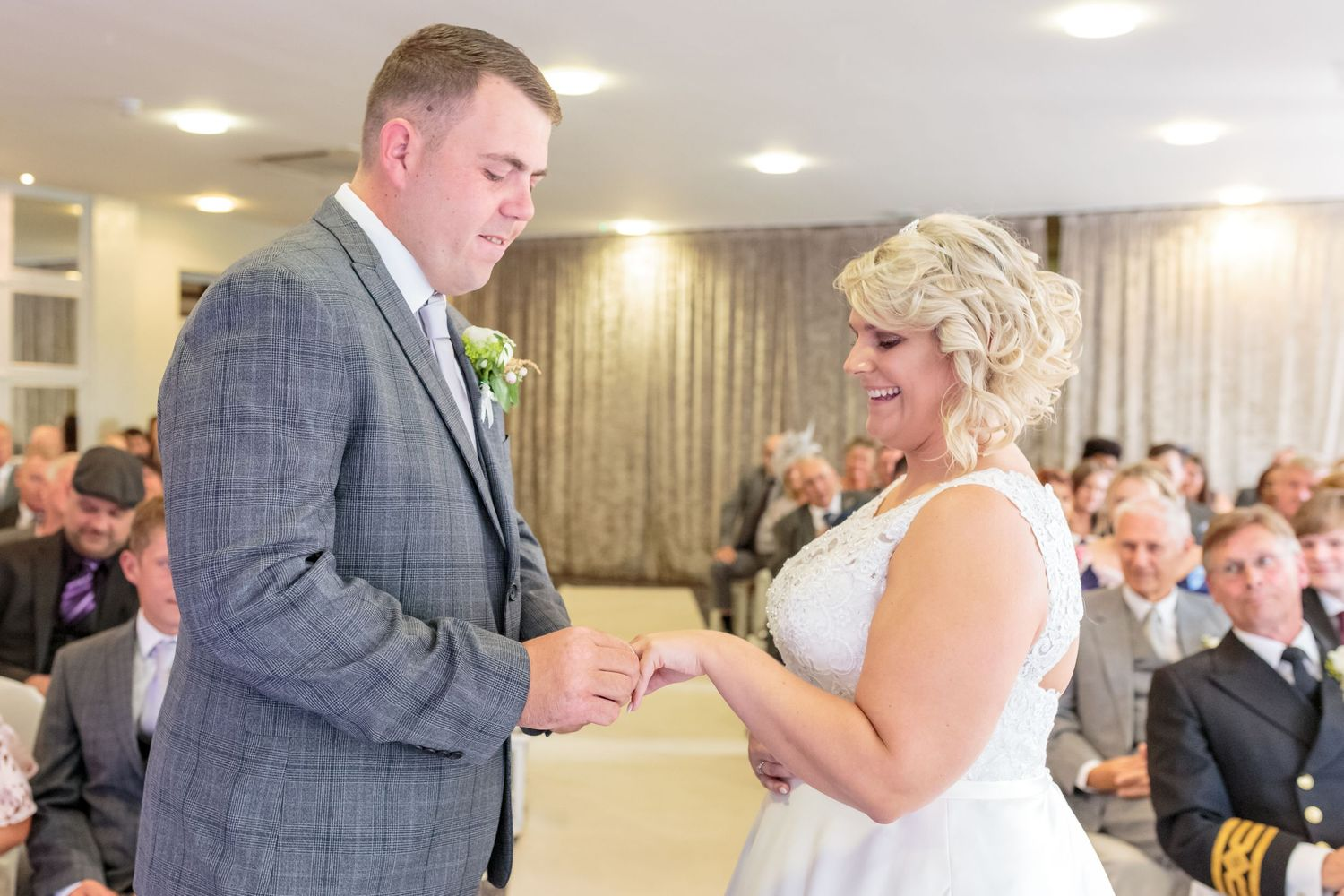 groom puts the ring on his brides favour as she looks down at her hand