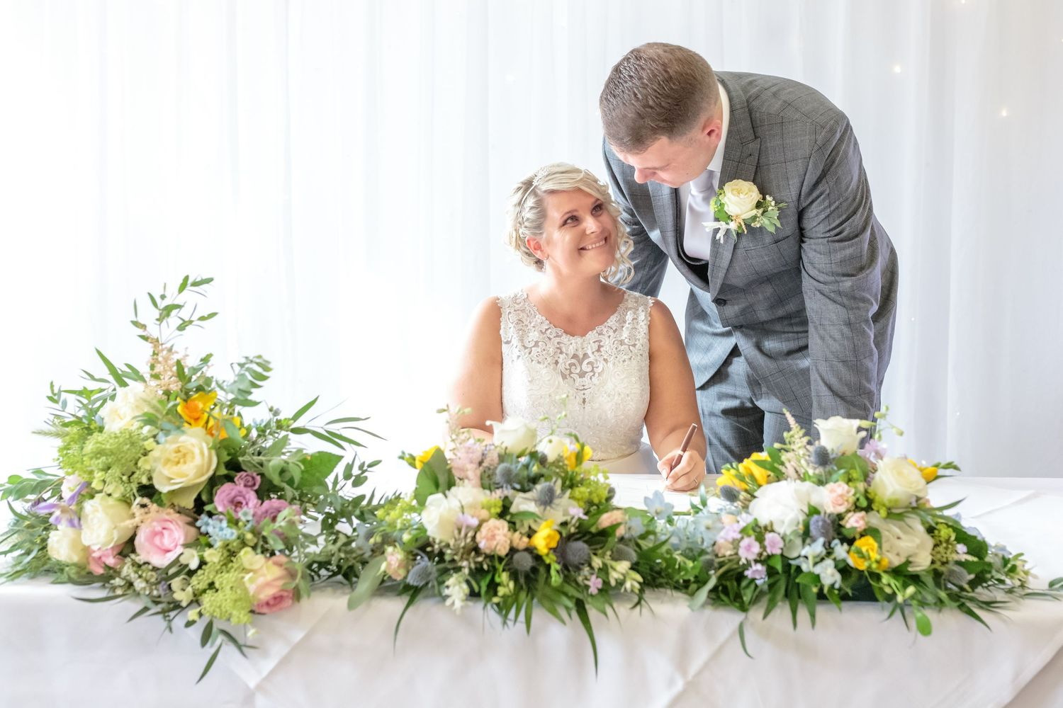bride sitting down looks up at her new husband leaning next to her as they sign the wedding register at ribby hall