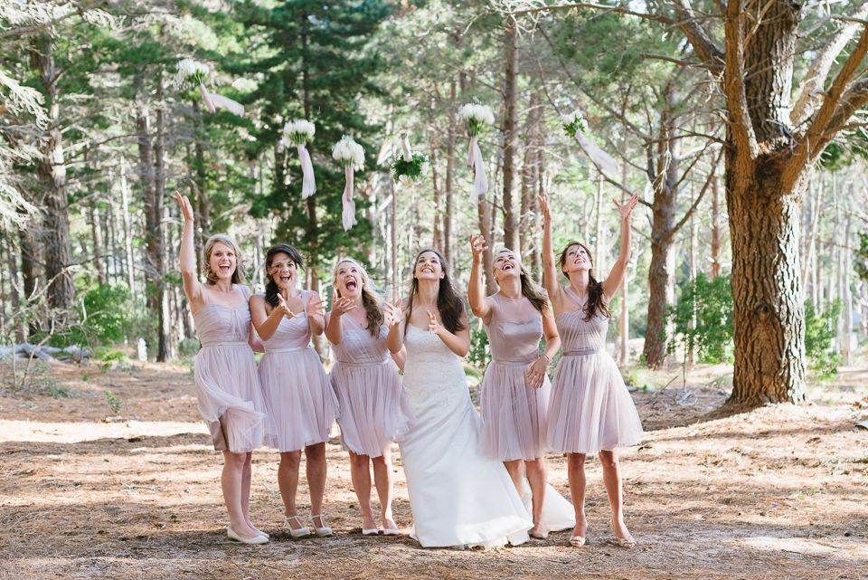 Bride and Bridesmaids tossing bouquets in the air at their Santa Cruz forest wedding.