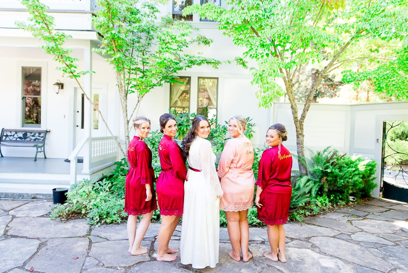 bridesmaids in red and blush stand next to bride on wedding day in September in California