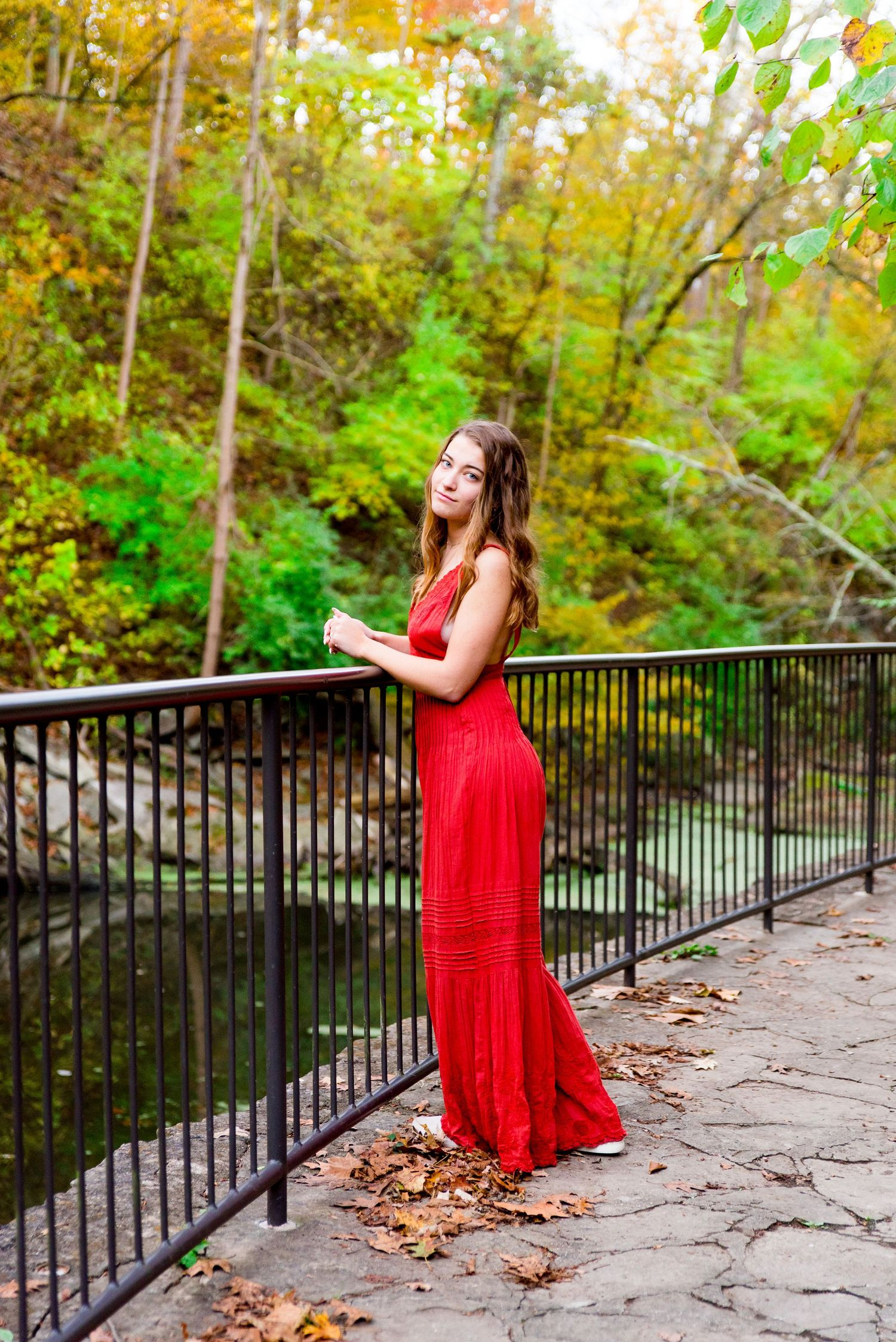 Senior Pictures in Chicago with a girl leaning over a bridge under fall colored trees next to a creek